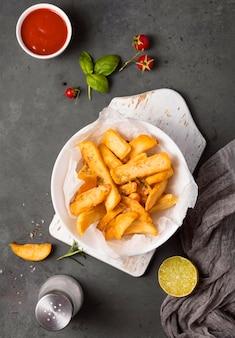 Vista superior de batatas fritas no prato com tomate e ketchup