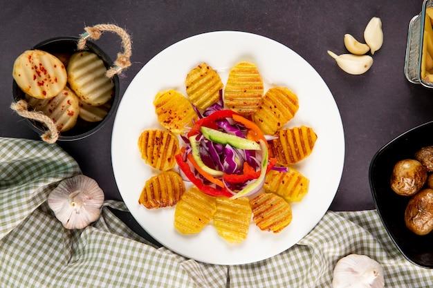 Vista superior de batatas grelhadas com pepino fresco, pimentão laranja, repolho roxo e alho em fundo cinza escuro