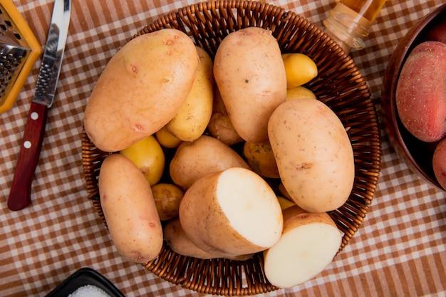Vista superior de batatas na cesta com faca no fundo de pano xadrez