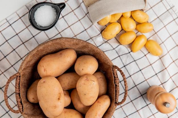 Vista superior de batatas na cesta com manteiga sal pimenta na superfície do pano xadrez