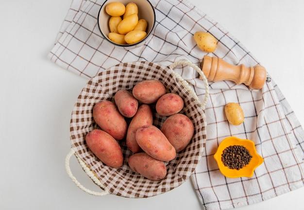 Vista superior de batatas na cesta e na tigela com sal pimenta no pano na superfície branca