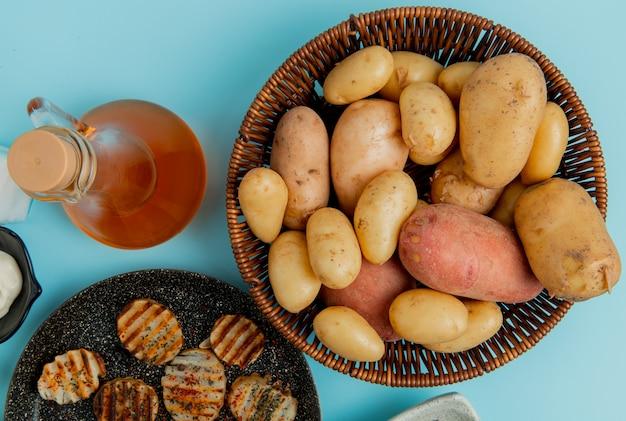 Vista superior de batatas na cesta e os fritos na frigideira com manteiga derretida na superfície azul