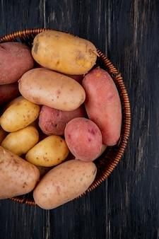 Vista superior de batatas na cesta na superfície de madeira