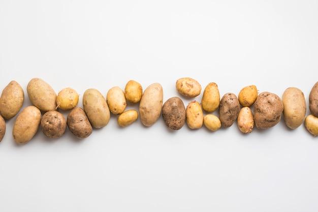 Vista superior de batatas naturais alinhadas
