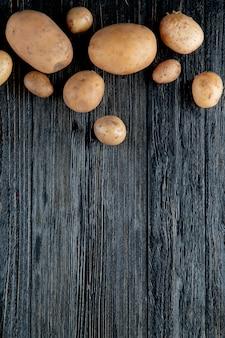 Vista superior de batatas no fundo de madeira com espaço de cópia