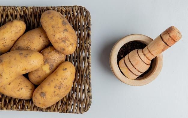Vista superior de batatas no prato de cesto e sementes de pimenta preta no triturador de alho na superfície branca