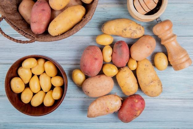 Vista superior de batatas novas na tigela e outros de diferentes tipos na cesta com sal triturador de alho e outras batatas na superfície de madeira