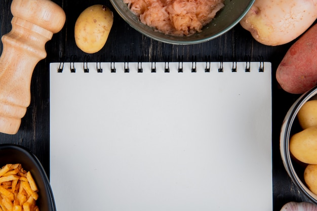 Vista superior de batatas raladas e fritas inteiras em torno do bloco de notas com sal na superfície de madeira com espaço de cópia