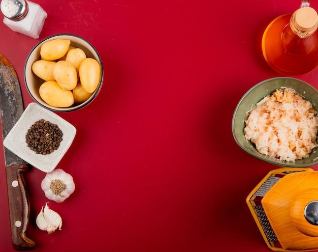 Vista superior de batatas raladas e inteiras em tigelas com faca de ralador de manteiga de sal pimenta no fundo do bordo com espaço de cópia