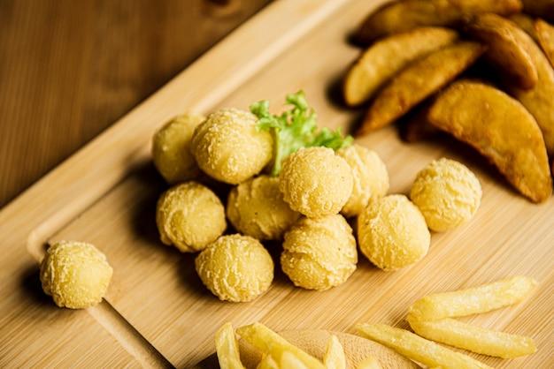 Vista superior de batatas sortidas. batatas fritas cozidas em uma placa de madeira, servidas com molho de tomate.