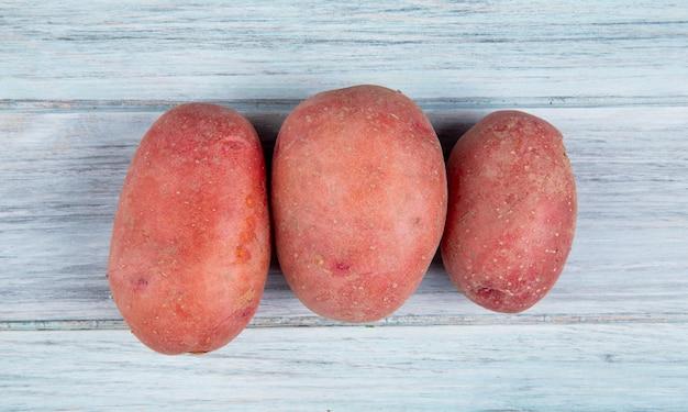 Vista superior de batatas vermelhas na superfície de madeira