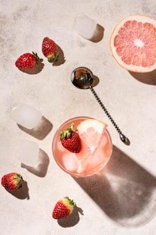 Vista superior de bebida alcoólica com toranja e morangos