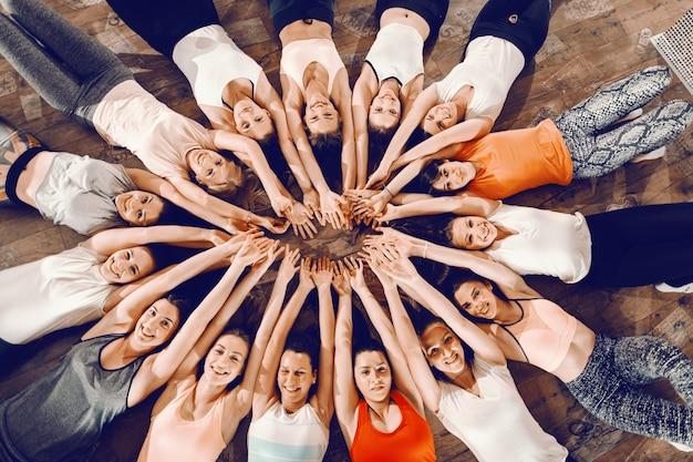 Vista superior de belas mulheres em forma deitadas em círculo no chão do ginásio e de mãos dadas acima das cabeças.