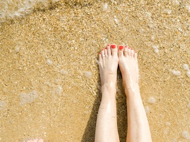 Vista superior de belos pés femininos com pedicure vermelho brilhante na areia da praia a onda do mar