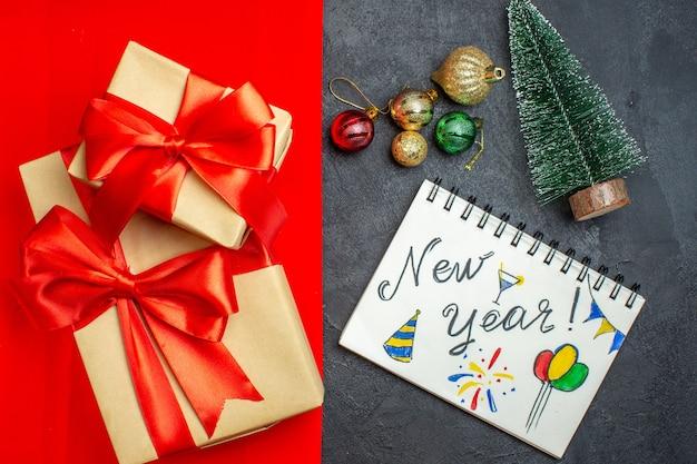 Vista superior de belos presentes com caderno de fita em forma de arco com desenhos de ano novo ao lado do acessório de decoração de ramos de pinheiro - árvore de natal em um fundo vermelho