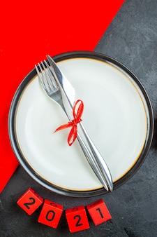 Vista superior de belos presentes e talheres em um prato com os números de uma mesa escura