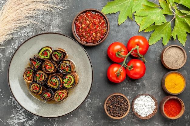 Vista superior de berinjela recheada rola diferentes especiarias adjika em pequenas tigelas e tomates em fundo cinza