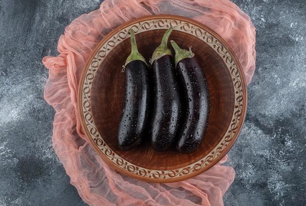 Vista superior de berinjela roxa orgânica fresca em uma placa de madeira