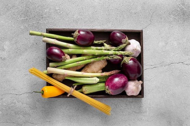 Vista superior de berinjelas, aspargos e espaguete cru