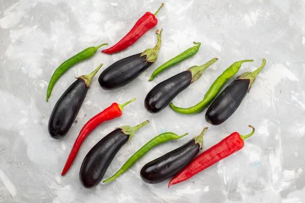 Vista superior de berinjelas pretas com pimentas na cor crua de alimentos com especiarias vegetais e vegetais brilhantes