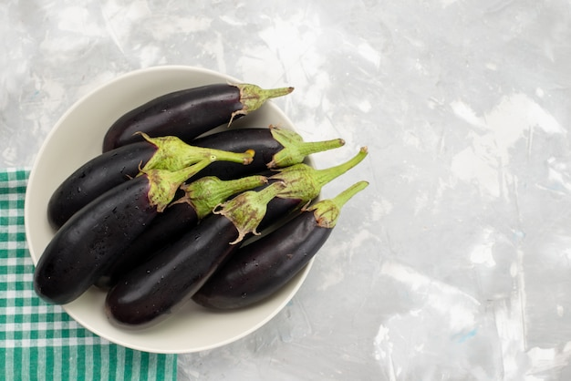 Vista superior de berinjelas pretas cruas dentro de um prato branco na árvore de refeição de alimentos crus frescos de vegetais