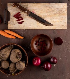 Vista superior de beterraba fresca em uma cesta com cebolas vermelhas e uma placa com uma faca e cenoura