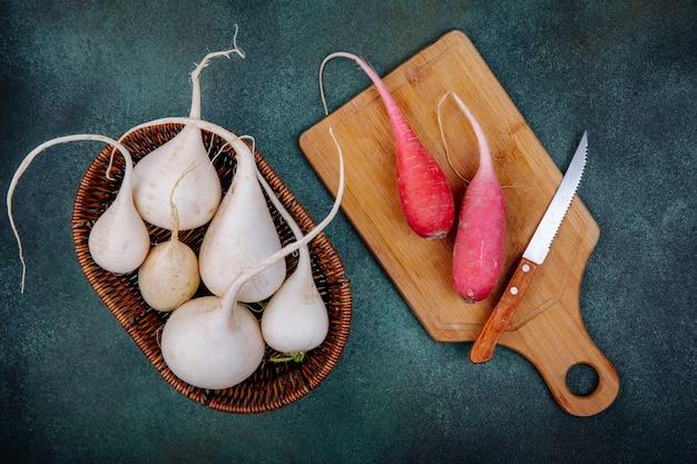Vista superior de beterrabas vegetais de raiz branca em um balde com beterrabas vermelhas rosadas em uma placa de cozinha de madeira com uma faca em uma superfície verde