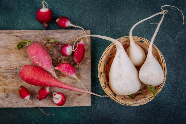 Vista superior de beterrabas vegetais de raiz vermelha rosada em uma placa de cozinha de madeira com rabanetes com beterrabas brancas em um balde em um fundo verde