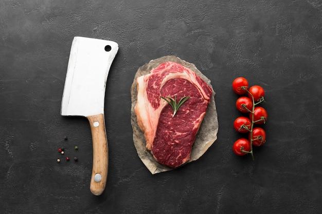 Vista superior de bife fresco com faca e tomate cereja