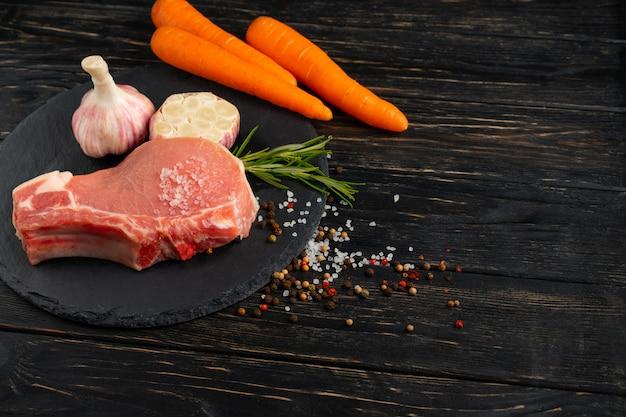 Vista superior de bifes de uma costeleta de carne de porco crua das partes com em uma placa de corte de pedra preta.