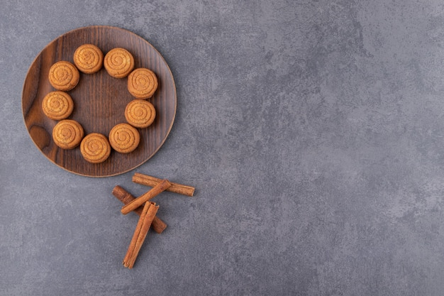 Vista superior de biscoitos caseiros com canela na placa de madeira.