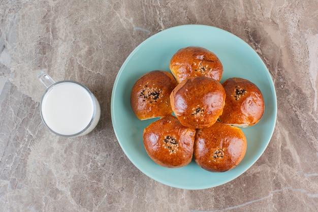 Vista superior de biscoitos caseiros na placa azul com leite.