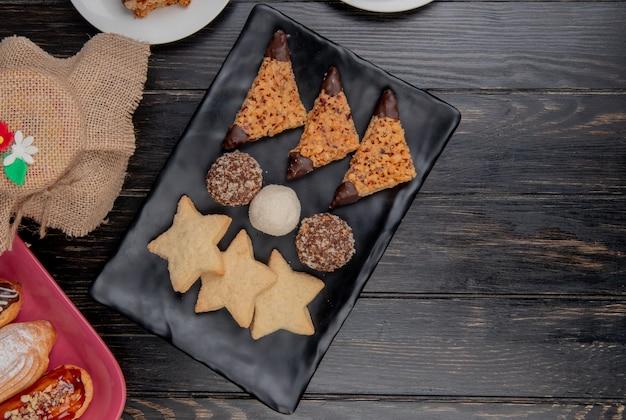 Vista superior de biscoitos com fatias de bolo no prato e bolos em fundo de madeira com espaço de cópia