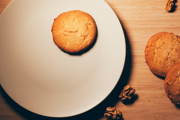 Vista superior de biscoitos com nozes, em um prato branco e mesa de madeira