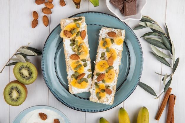 Vista superior de biscoitos crocantes com creme de queijo, fatias de banana, amêndoa e sementes de abóbora em um prato na madeira branca