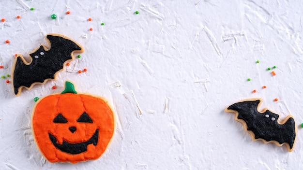 Vista superior de biscoitos de açúcar de glacê de gengibre de confeiteiro de halloween com decoração festiva de halloween em fundo branco com espaço de cópia e layout plano leigo