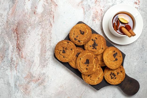 Vista superior de biscoitos de areia deliciosos, doces perfeitos para uma xícara de chá na superfície branca