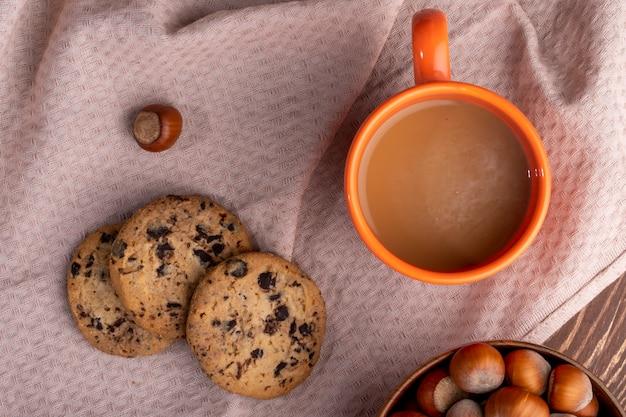 Vista superior de biscoitos de aveia com gotas de chocolate e uma caneca de bebida de cacau numa toalha de mesa
