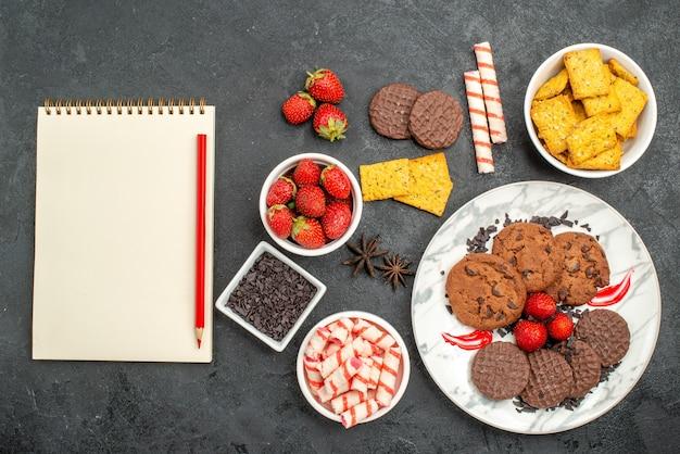 Vista superior de biscoitos de chocolate saborosos com diferentes lanches em fundo escuro foto de biscoitos doces