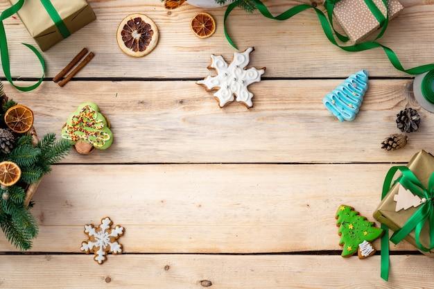 Vista superior de biscoitos de gengibre em uma mesa de madeira com enfeites