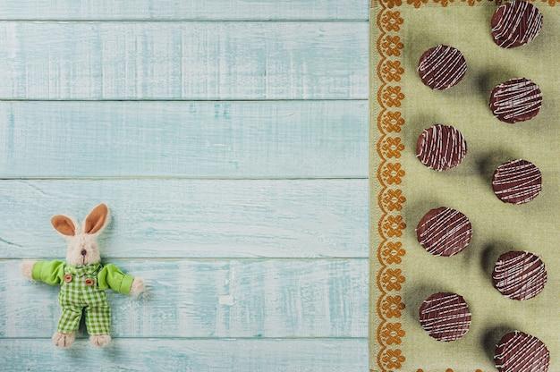 Vista superior de biscoitos de mel caseiros brasileiros com cobertura de chocolate em fundo de madeira com coelho de pelúcia e espaço de cópia - paes de mel