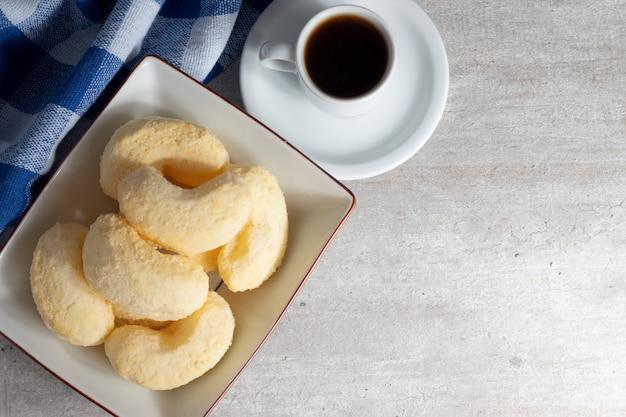 Vista superior de biscoitos de queijo brasileiro e café.