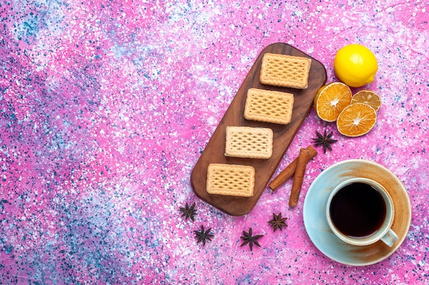 Vista superior de biscoitos de waffle com recheio de creme de frutas e chá na superfície rosa claro
