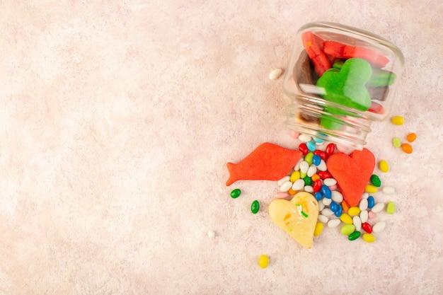 Vista superior de biscoitos deliciosos coloridos diferentes formados dentro pode com doces na superfície rosa