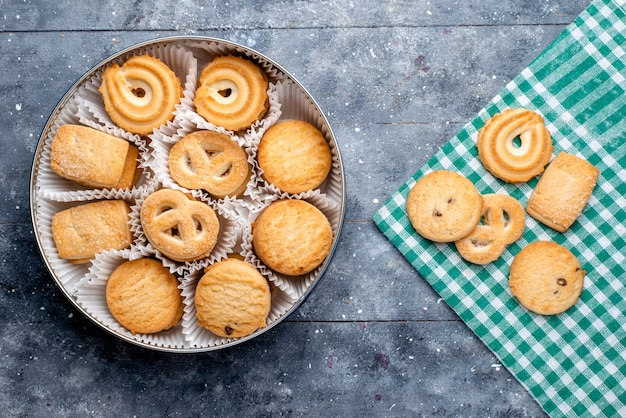 Vista superior de biscoitos deliciosos formados de forma diferente dentro da embalagem redonda na mesa cinza, biscoito de biscoito de bolo doce de açúcar
