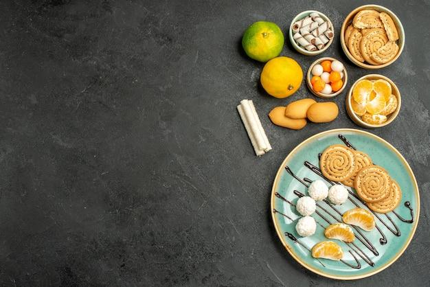 Vista superior de biscoitos doces com balas e tangerinas em fundo cinza