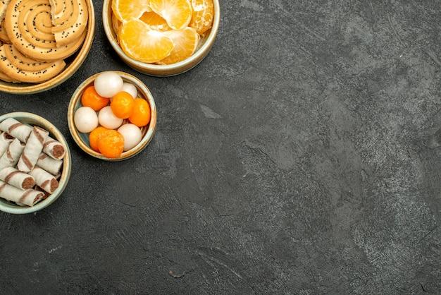 Vista superior de biscoitos doces com balas e tangerinas na mesa cinza Foto gratuita