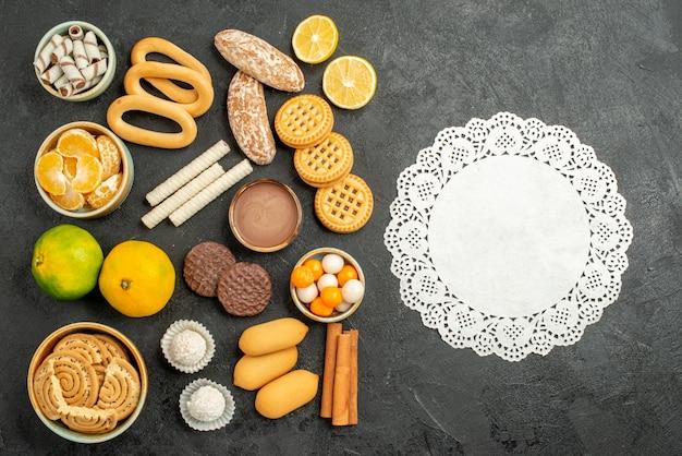 Vista superior de biscoitos doces com biscoitos e frutas em fundo cinza