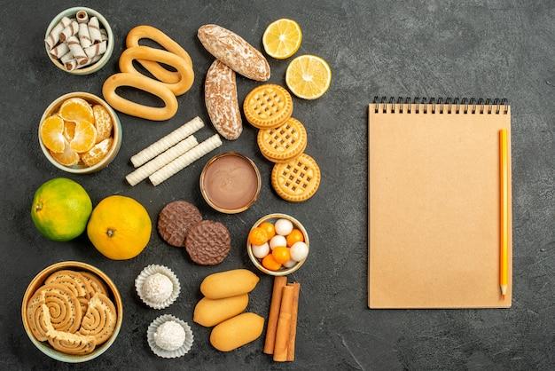 Vista superior de biscoitos doces com frutas e biscoitos em fundo cinza