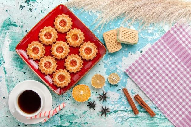 Vista superior de biscoitos doces com geleia de laranja e uma xícara de chá no fundo azul claro